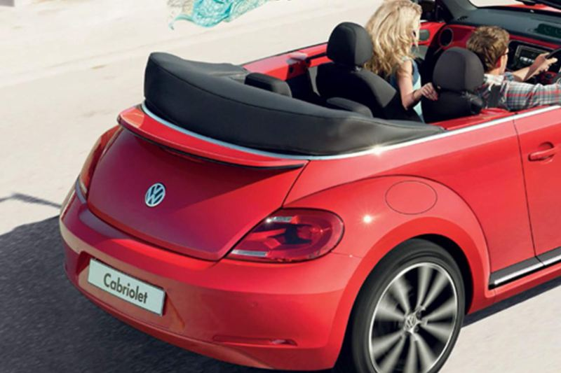 Rear shot of a red Volkswagen Beetle Cabriolet, a couple driving next to the beach with the roof down.