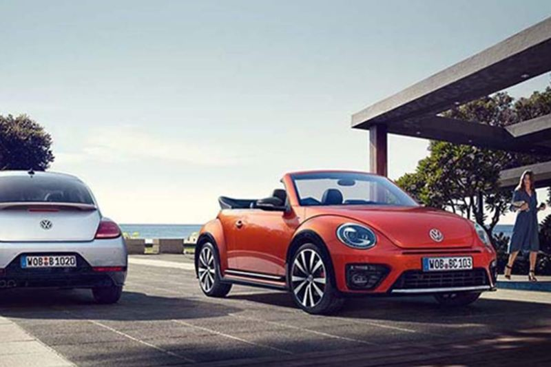 A orange Volkswagen Beetle Cabriolet, parked next to a beach on a promenade.