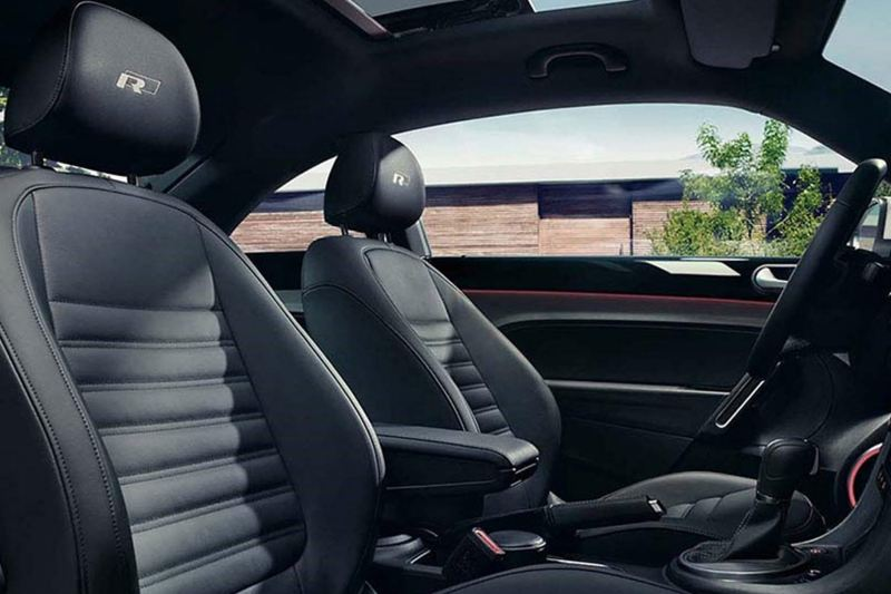 Front interior shot of a Volkswagen Beetle Cabriolet, a wooden building can be seen through the drivers door.