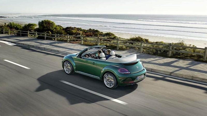 A couple driving a green Beetle Cabriolet