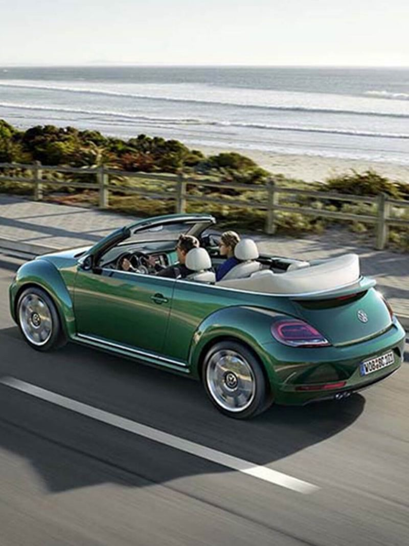 A couple driving a green Volkswagen Beetle Cabriolet, on a coastal road.