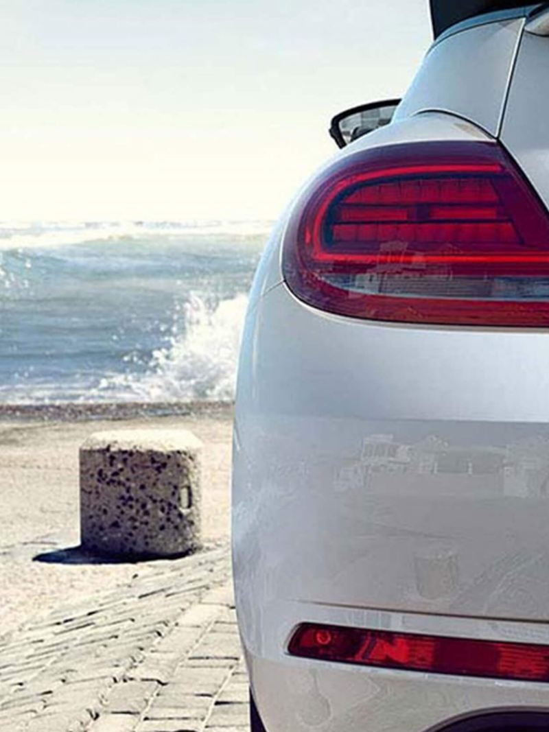 Rear shot of a white Volkswagen Beetle with the sea in the background.