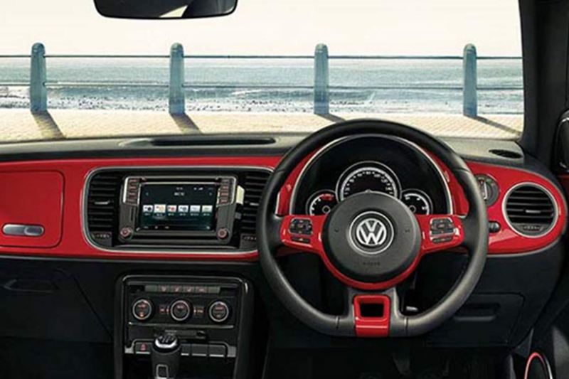 Interior dashboard and steering wheel shot of a Volkswagen Beetle Cabriolet, on a promenade with the sea in front.