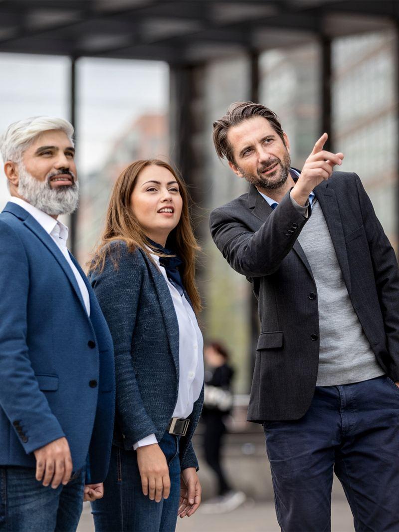 Eine Frau und zwei Männer besichtigen ein Firmengebäude