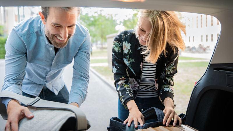 Eine Frau und ein Mann verstauen ihre Taschen im Kofferraum