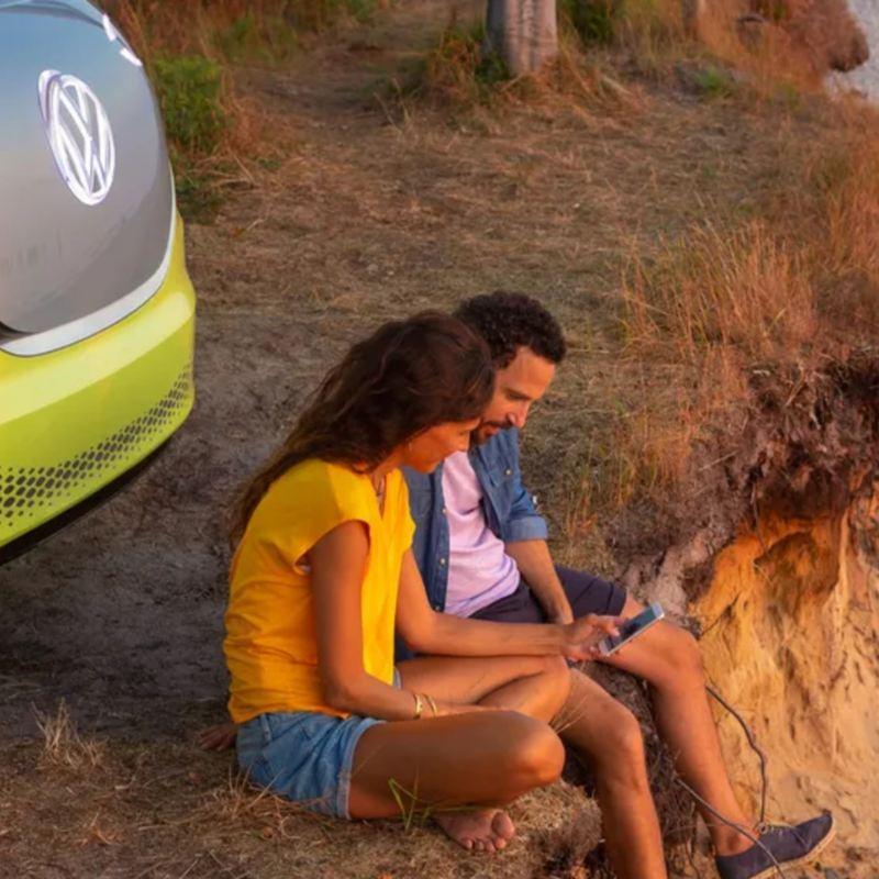 Combi eléctrica de Volkswagen estacionada detrás de pareja sentada en piso