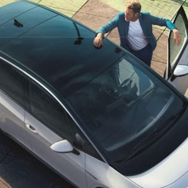 Hombre entrando a auto eléctrico Volkswagen, la gama de autos para movilidad limpia VW