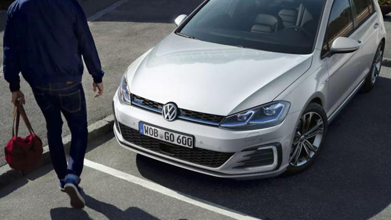Auto híbrido compacto de Volkswagen color gris platinado estacionado