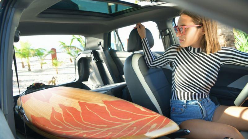 Mujer dentro de Nuevo T-Cross acomodando tabla de surf en interior espacioso del SUV