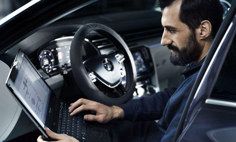 Mekaniker sitter i en VW Transportbil och utför service