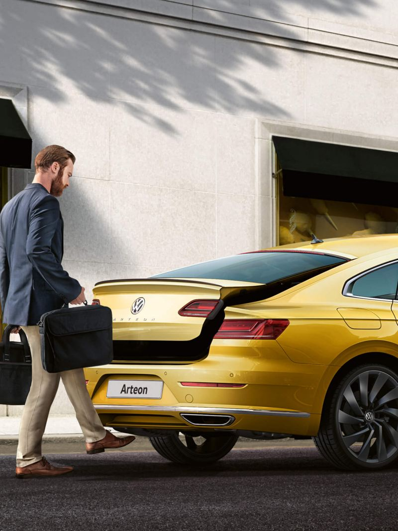 A man with bags using the hands-free sensors to open the boot of a yellow Volkswagen Arteon.