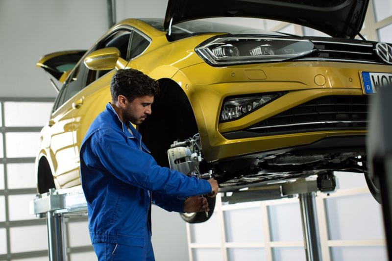 A VW employee changes the Volkswagen Brakes on this yellow VW