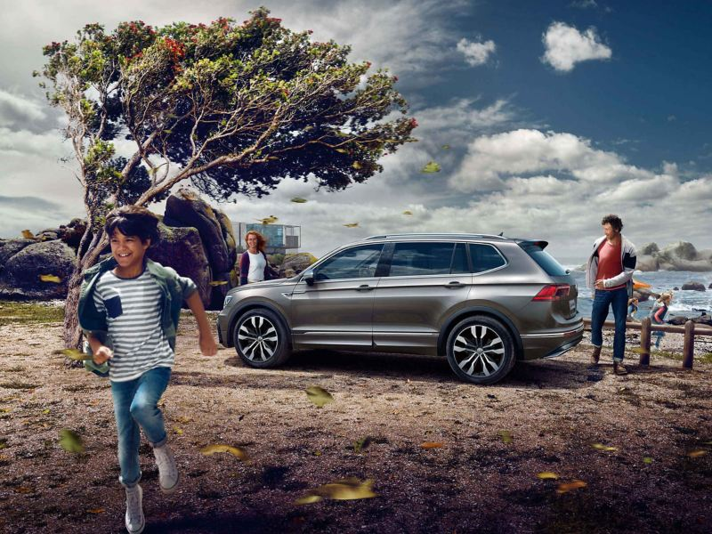 A boy running with a couple and a Tiguan in a background