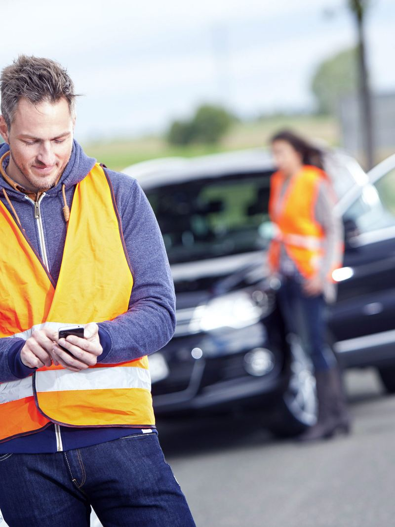 A man wearing a high vis waistcoat on his phone