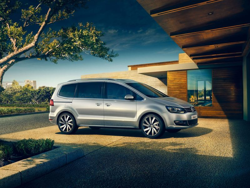 A silver Volkswagen Sharan, parked on the drive of a single story wooden house, trees in the background.