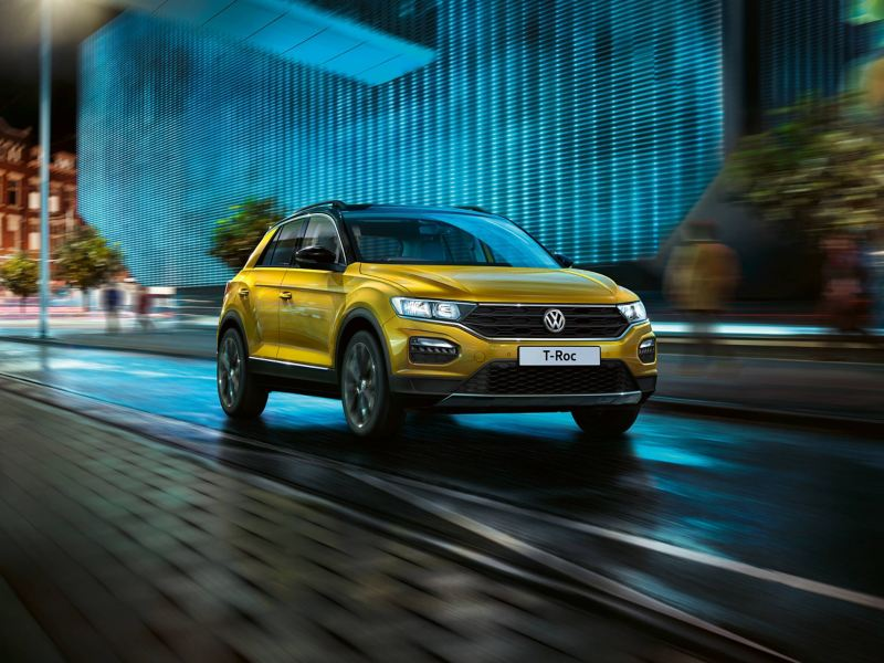 A yellow Volkswagen T-Roc driving through a well lit city street at night.