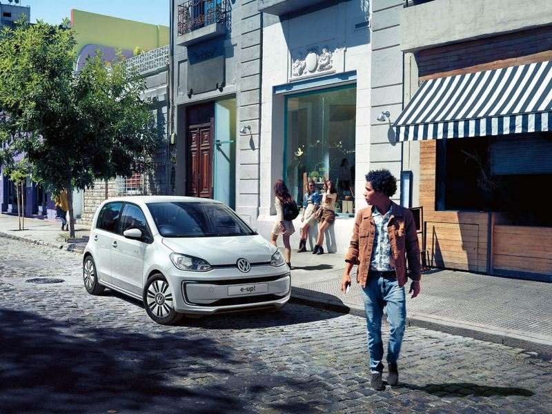 A white 5-door Volkswagen e-up! parked outside shops on a tree-lined cobbled street.