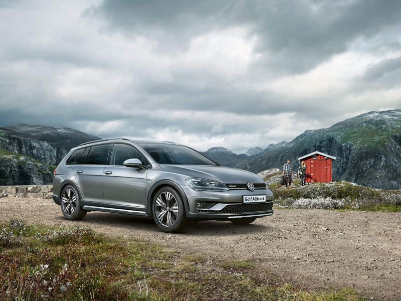 A silver Volkswagen Golf Alltrack Estate, on a mountain with a densely cloudy sky.