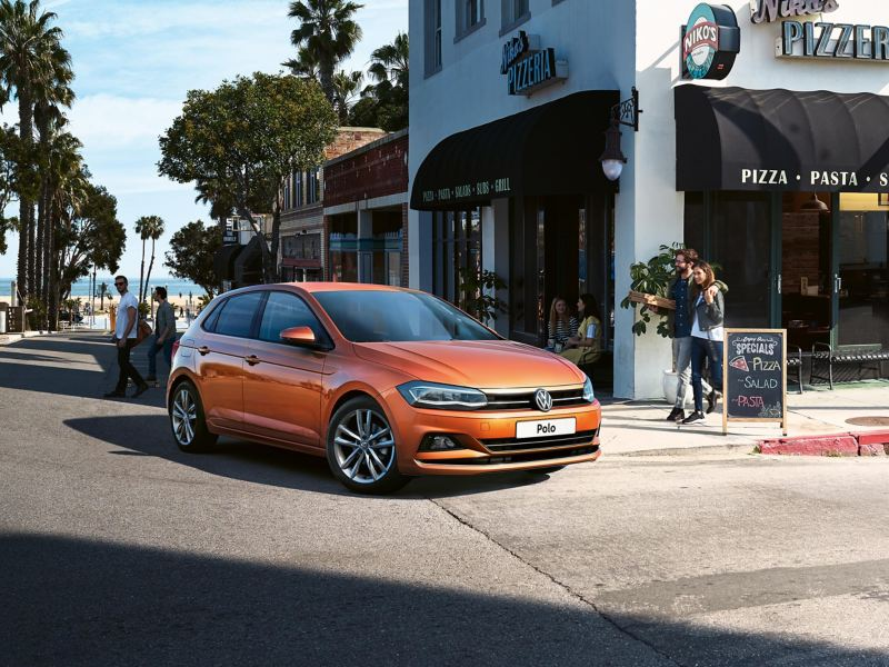 An orange Volkswagen Polo turning a street corner, in front of a coastal pizzeria.