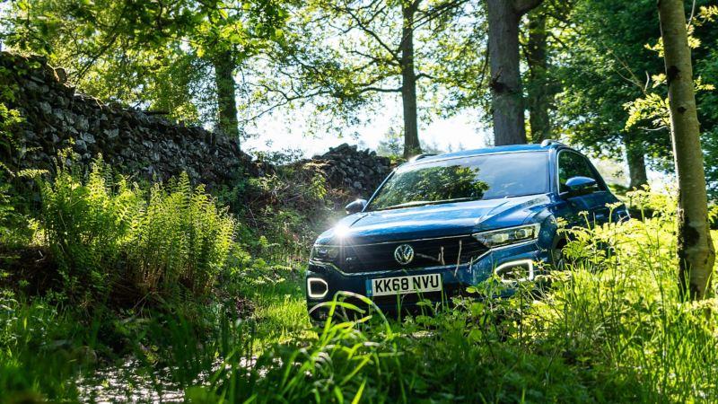 A blue Volkswagen T-Roc driving through green woodland.