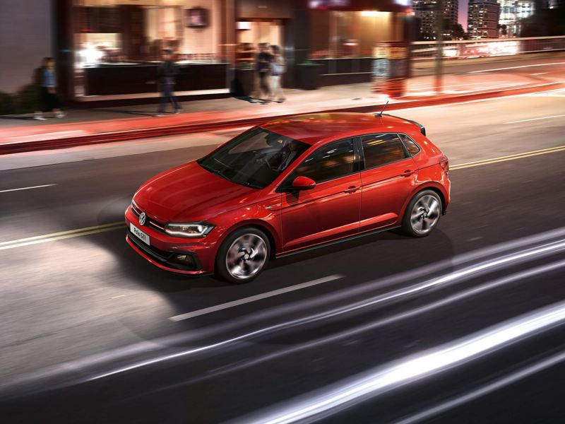 A red Volkswagen Polo driving through a city street in the evening.