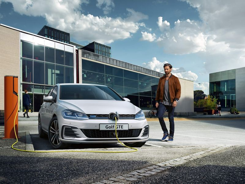 A man charging his silver Volkswagen Golf GTE at a charge point, surrounded by glass-fronted buildings.