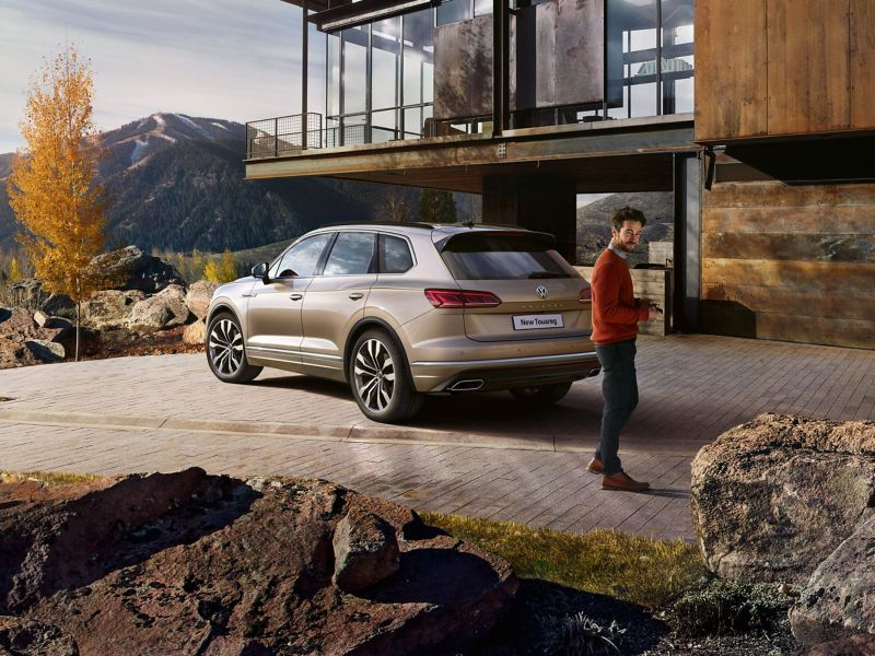 A man walking from bronze Volkswagen Touareg outside a house in the mountains.