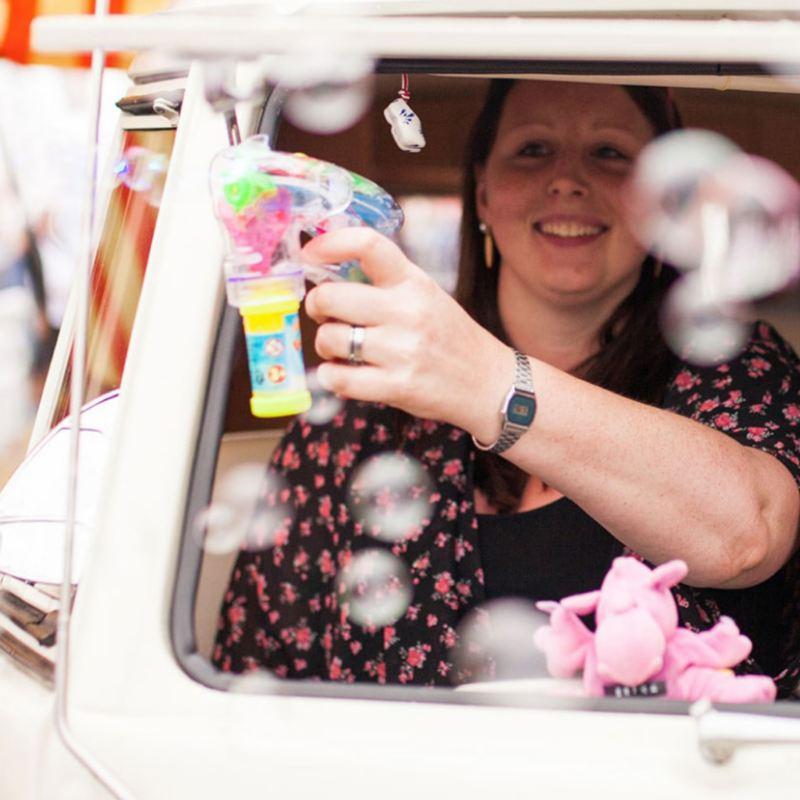 Eine Besucherin des Bulli Summer Festival schaut aus ihrem bunt geschmückten Bulli.