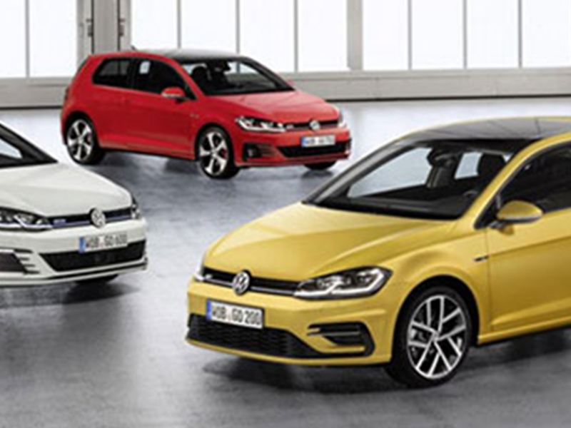 A red, white and yellow Volkswagen Golf's, in a retail showroom.