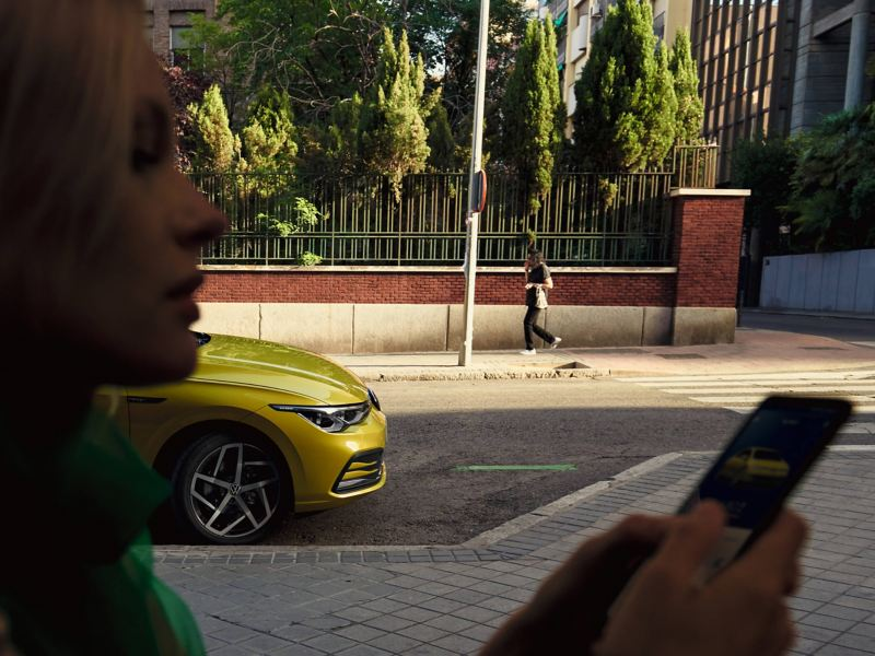 The woman using a phone while standing on the street in front of a yellow Golf 8.