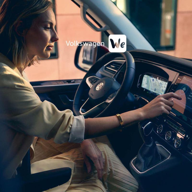 Volkswagen We logo over woman using touchscreen in T6.1