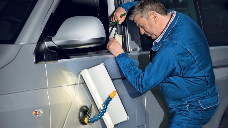 technician repairing a damage to a van's front door