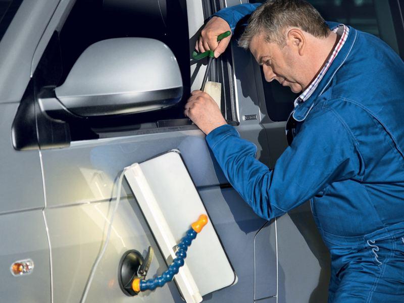 Van technician fixing passenger window