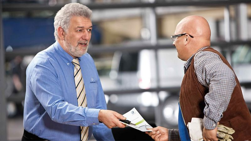 sales assistant handing the van's maintenance booklet to a customer
