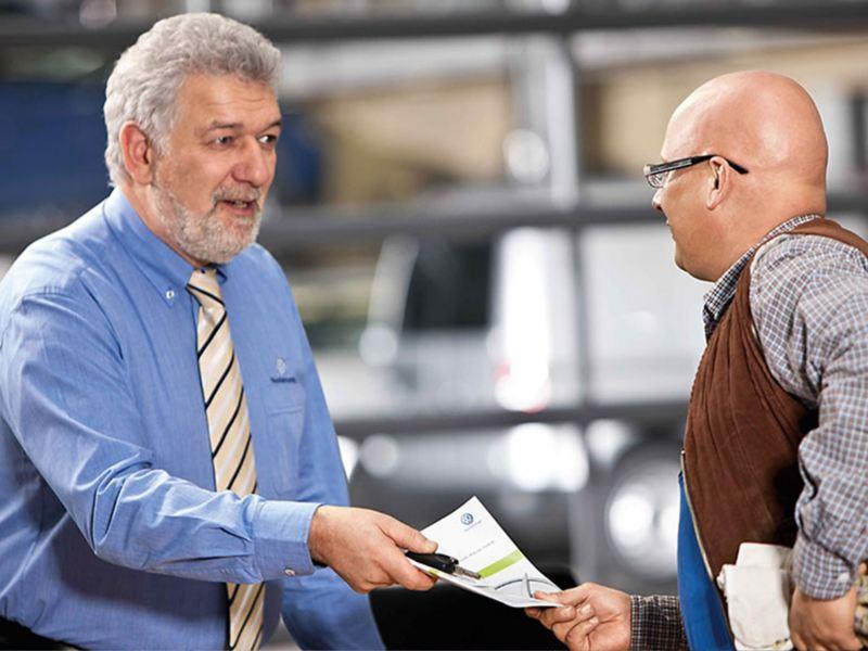 Van dealer handing customer form