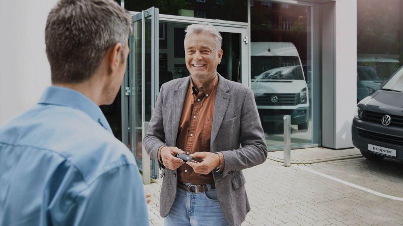 Customer and van dealer outside Volkswagen dealership