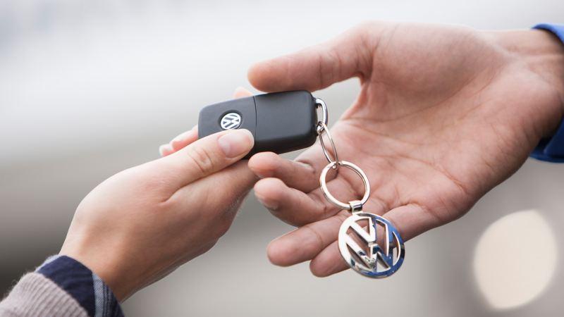 Two hands handing over car keys