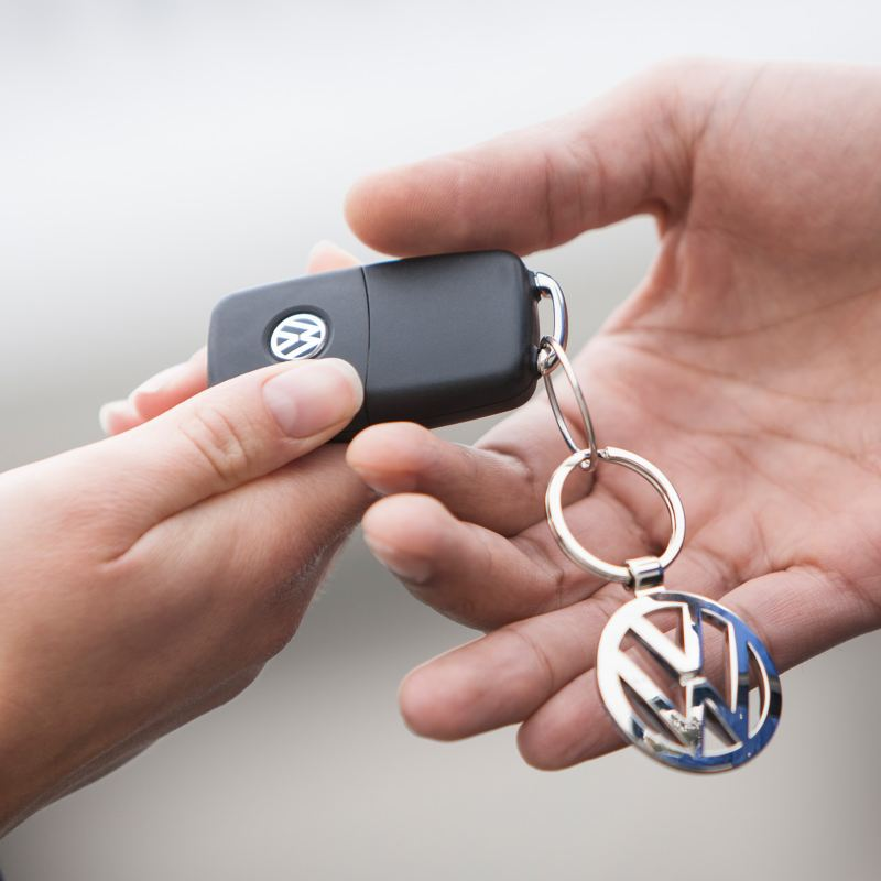 Close-up of one hand passing VW car keys to another hand.