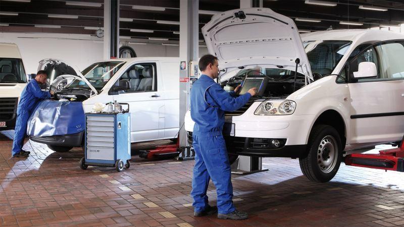 Two technicians perform van servicing