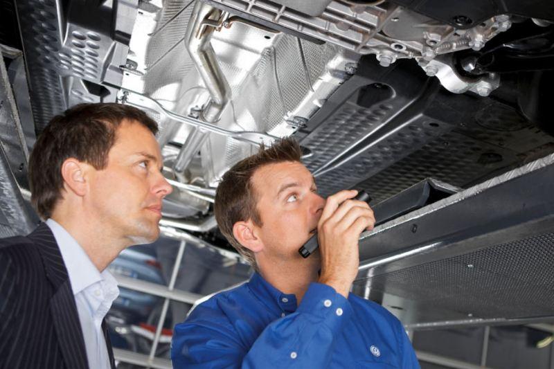 technician and manager inspecting VW van underside