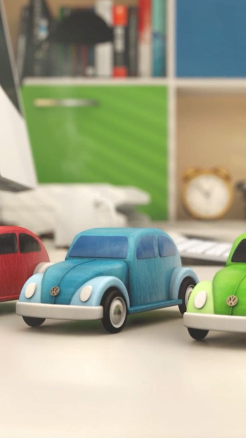 Three toy Beetles on a desk.