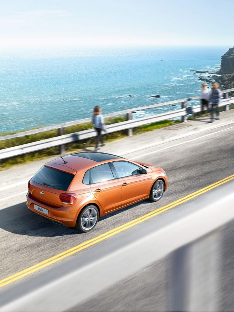 A orange Volkswagen Polo driving on the road near the coast.