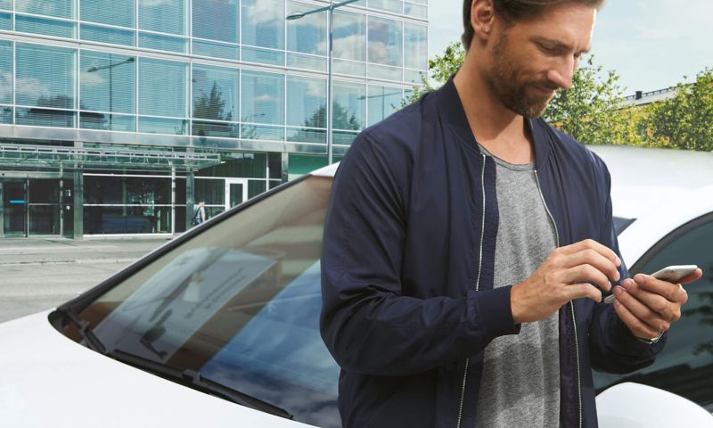 Man using phone in front of his a white Volkswagen Golf GTE.