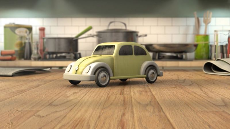 A green toy Volkswagen Beetle, on a kitchen work surface.