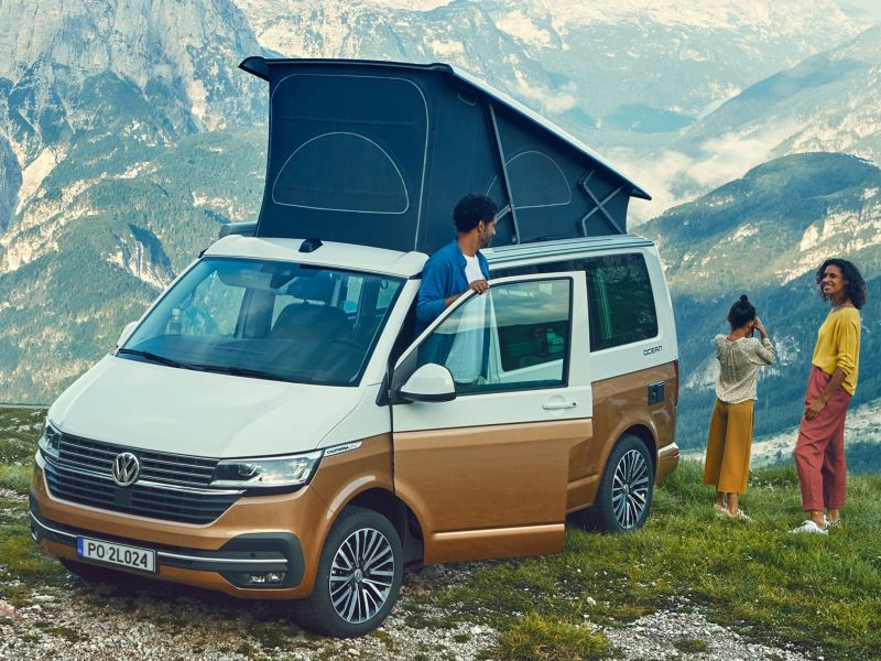 Rodzina w Volkswagen California 6.1 w punkcie widokowym w górach.