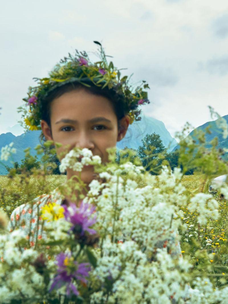 Flick på ett blomsterfält framför en VW California 6.1