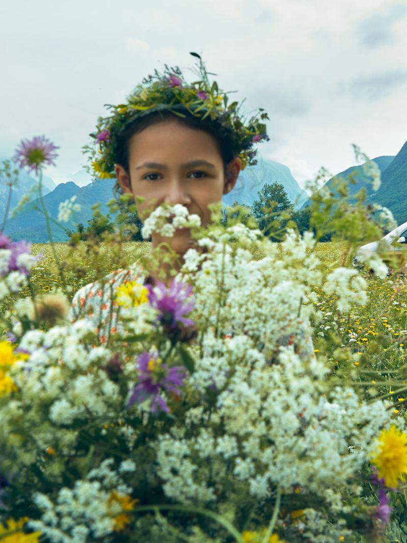 Ein Mädchen steht in einer Blumenwiese; im Hintergrund steht ein Volkswagen California 6.1.