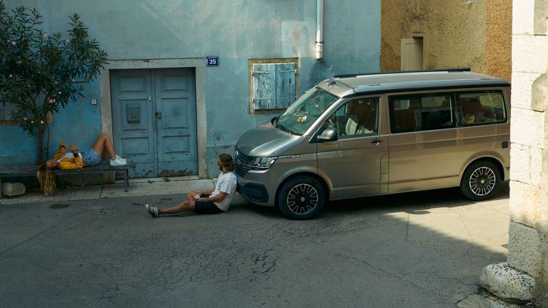 Un uomo seduto a terra davanti a California 6.1 Beach Volkswagen, visto lateralmente e parcheggiato di fronte a una casa.