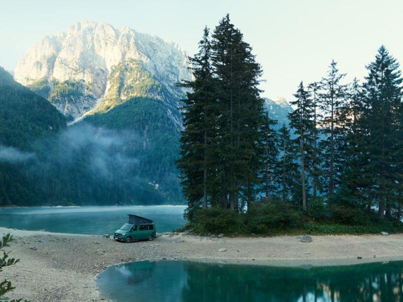 Un California 6.1 Beach Volkswagen parcheggiato in riva a un lago di montagna.