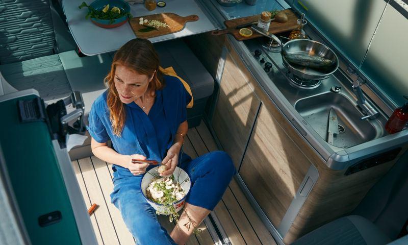 Kobieta siedzi na podłodze kuchni w Volkswagen California 6.1.